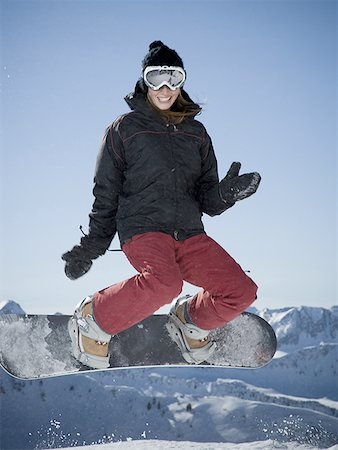 Low angle view of a young woman performing a stunt on a snowboard Stock Photo - Premium Royalty-Free, Code: 640-01364660