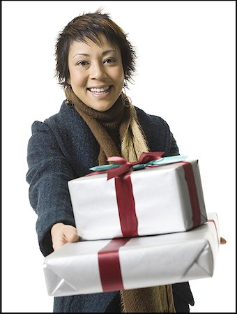 Portrait of a young woman holding gifts Stock Photo - Premium Royalty-Free, Code: 640-01364975