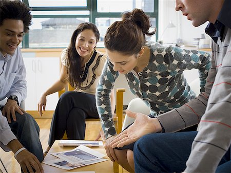 Four people discussing ad layouts Stock Photo - Premium Royalty-Free, Code: 640-01365063