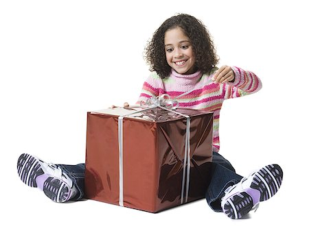 Girl unwrapping a gift Stock Photo - Premium Royalty-Free, Code: 640-01365596