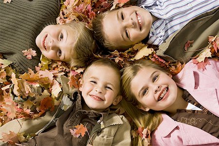 pile leaves playing - Young kids playing in a pile of fallen leaves Stock Photo - Premium Royalty-Free, Code: 640-01366112
