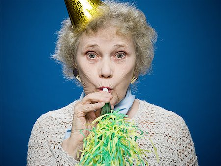 Older woman wearing a party hat blows a noisemaker Stock Photo - Premium Royalty-Free, Code: 640-01366170