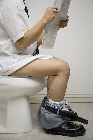 Mid section view of a young man sitting on the toilet seat reading a newspaper Stock Photo - Premium Royalty-Free, Code: 640-01366460