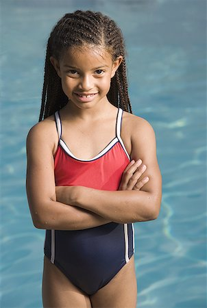 Portrait of a girl standing at a swimming pool and smiling Stock Photo - Premium Royalty-Free, Code: 640-01366515