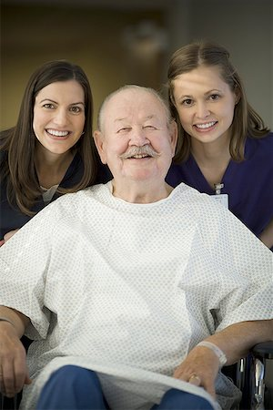 Portrait of two female nurses helping a male patient sitting on a wheel chair Stock Photo - Premium Royalty-Free, Code: 640-01366618