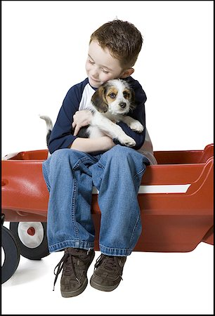 people kissing little boys - Close-up of a boy sitting on a wagon hugging a puppy Stock Photo - Premium Royalty-Free, Code: 640-01360603