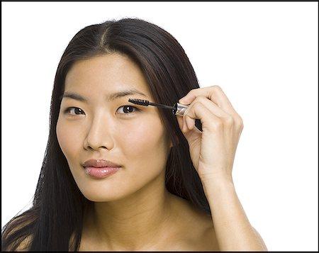 Portrait of a woman applying mascara on her eyelashes Stock Photo - Premium Royalty-Free, Code: 640-01360621