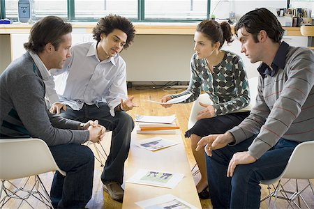 Four people discussing ad layouts Stock Photo - Premium Royalty-Free, Code: 640-01360790