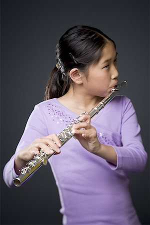 Close-up of a girl playing the flute Stock Photo - Premium Royalty-Free, Code: 640-01361169