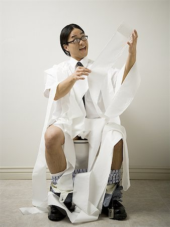 Close-up of a young man sitting on a toilet Stock Photo - Premium Royalty-Free, Code: 640-01361177