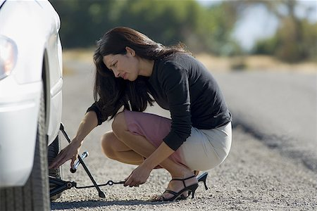 Profile of a woman fixing a flat tire Stock Photo - Premium Royalty-Free, Code: 640-01361196