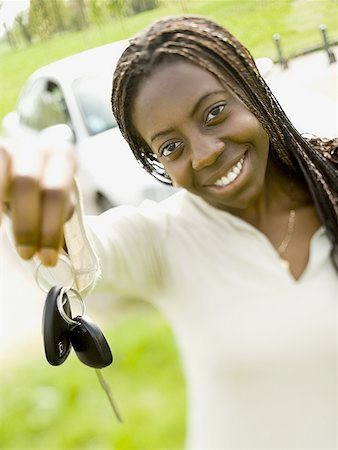 Portrait of a teenage girl holding a car key and smiling Stock Photo - Premium Royalty-Free, Code: 640-01361501