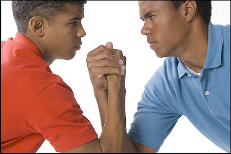 Close-up of two young men arm wrestling Stock Photo - Premium Royalty-Free, Code: 640-01361875