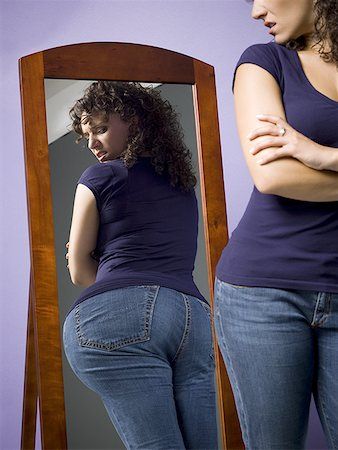 Young woman looking at her buttocks in the mirror Stock Photo - Premium Royalty-Free, Code: 640-01362029