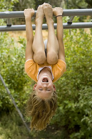 Girl hanging upside down from a jungle gym Stock Photo - Premium Royalty-Free, Code: 640-01362595
