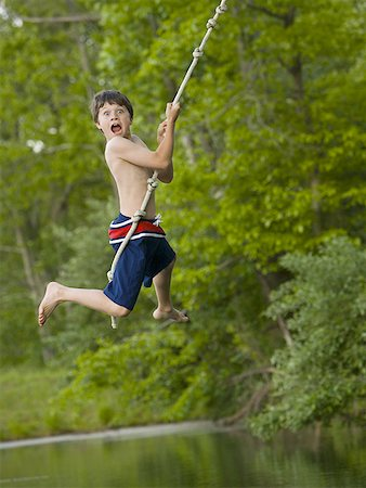 Portrait of a boy swinging on a rope Stock Photo - Premium Royalty-Free, Code: 640-01362943