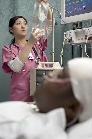 Female nurse checking an intravenous drip Stock Photo - Premium Royalty-Free, Code: 640-01362980