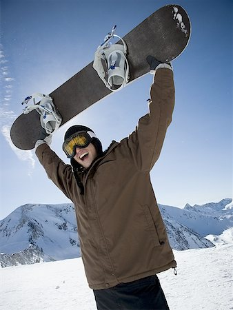 Low angle view of a young man lifting a snowboard and shouting Stock Photo - Premium Royalty-Free, Code: 640-01363281