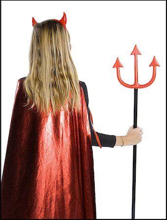 Rear view of a teenage girl wearing a devil costume holding a pitchfork Stock Photo - Premium Royalty-Free, Code: 640-01363566