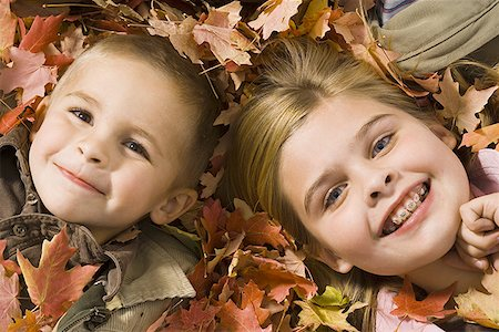 pile leaves playing - Young children playing in pile of fallen leaves Stock Photo - Premium Royalty-Free, Code: 640-01363768