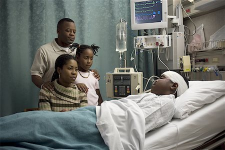 Parents and their daughter looking at a teenage boy in the hospital Stock Photo - Premium Royalty-Free, Code: 640-01363782