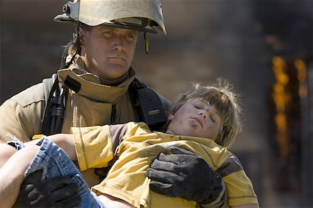 Firefighter carrying a wounded boy Stock Photo - Premium Royalty-Free, Code: 640-01363833