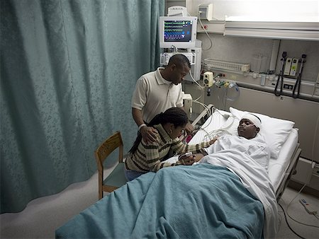 High angle view of parents looking at their teenage son in the hospital Stock Photo - Premium Royalty-Free, Code: 640-01363966