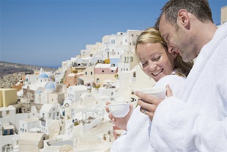 Couple in bathrobes with cups smiling with scenic village in background Stock Photo - Premium Royalty-Free, Code: 640-01574811