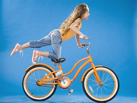 forward - Girl on orange bicycle kneeling on seat with foot up Stock Photo - Premium Royalty-Free, Code: 640-01574949