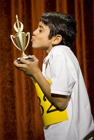 preteen kissing - Boy kissing trophy cup Stock Photo - Premium Royalty-Free, Code: 640-01575002