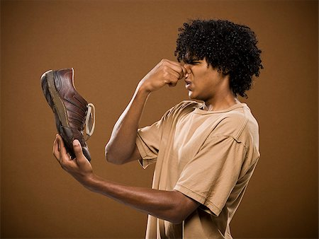 smelly - young man in a brown shirt holding a shoe and his nose. Stock Photo - Premium Royalty-Free, Code: 640-02656871