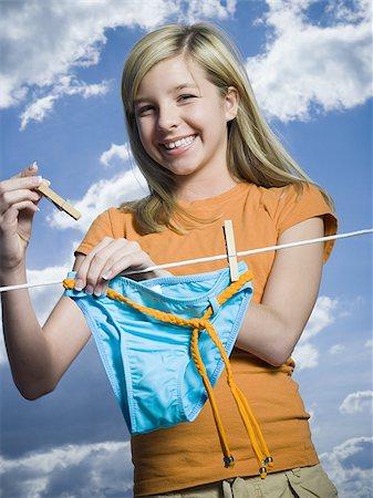 Portrait of a teenage girl drying a bikini bottom on a clothesline Stock Photo - Premium Royalty-Free, Code: 640-02764421