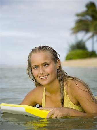 Portrait of a teenage girl smiling on a boogie board Stock Photo - Premium Royalty-Free, Code: 640-02764469
