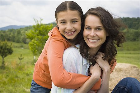 daughter kissing mother - Portrait of a girl hugging her mother from behind Stock Photo - Premium Royalty-Free, Code: 640-02764694