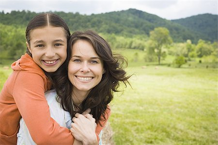 daughter kissing mother - Portrait of a girl hugging her mother from behind Stock Photo - Premium Royalty-Free, Code: 640-02764692