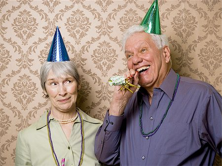 A senior man standing with a senior woman and blowing a party favor Stock Photo - Premium Royalty-Free, Code: 640-02764796