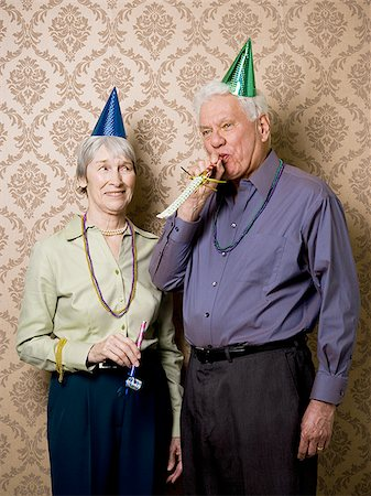 A senior man standing with a senior woman and blowing a party favor Stock Photo - Premium Royalty-Free, Code: 640-02764797