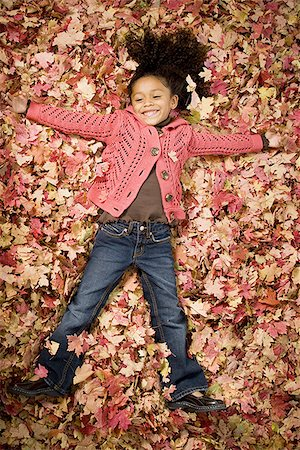 pile leaves playing - Young girl playing in fallen leaves Stock Photo - Premium Royalty-Free, Code: 640-02764971