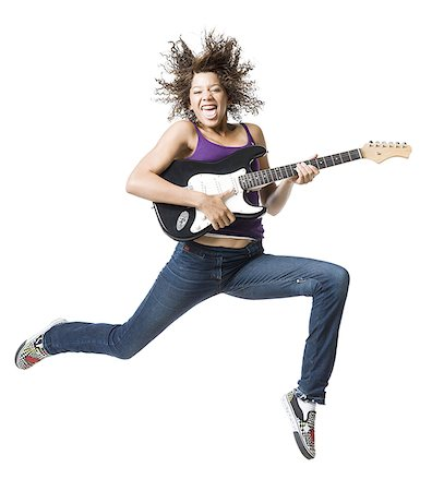 Girl with braces and guitar leaping and sticking tongue out Stock Photo - Premium Royalty-Free, Code: 640-02765364