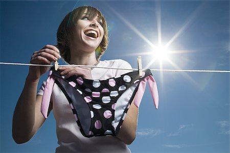 Low angle view of a teenage girl drying a bikini bottom on a clothesline Stock Photo - Premium Royalty-Free, Code: 640-02765868