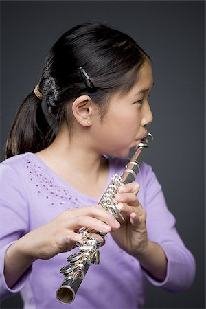 Close-up of a girl playing the flute Stock Photo - Premium Royalty-Free, Code: 640-02766461