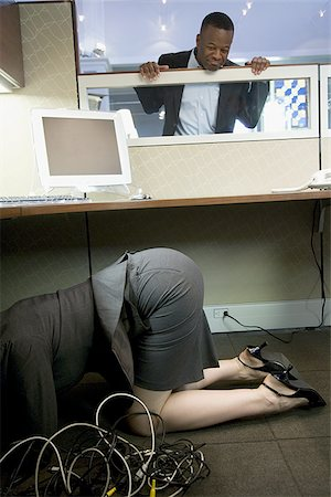 Businesswoman crouching under a computer desk with a businessman looking at her Stock Photo - Premium Royalty-Free, Code: 640-02766757