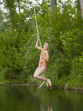 Portrait of a girl swinging on a rope Stock Photo - Premium Royalty-Free, Code: 640-02767080