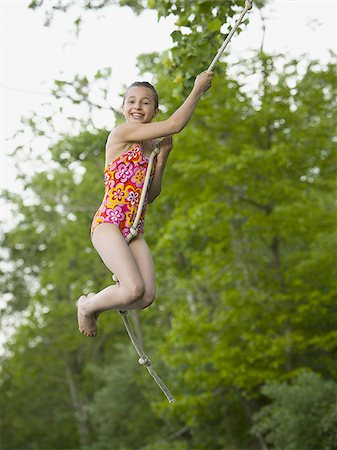 Portrait of a girl swinging on a rope Stock Photo - Premium Royalty-Free, Code: 640-02767081