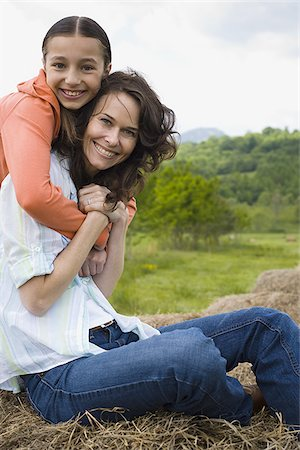 Portrait of a girl hugging her mother from behind Stock Photo - Premium Royalty-Free, Code: 640-02767569