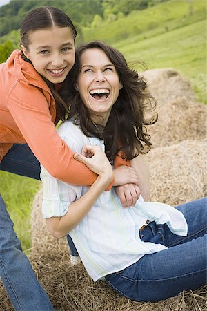 Portrait of a girl hugging her mother from behind Stock Photo - Premium Royalty-Free, Code: 640-02767570