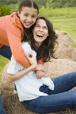 Portrait of a girl hugging her mother from behind Stock Photo - Premium Royalty-Free, Code: 640-02767571