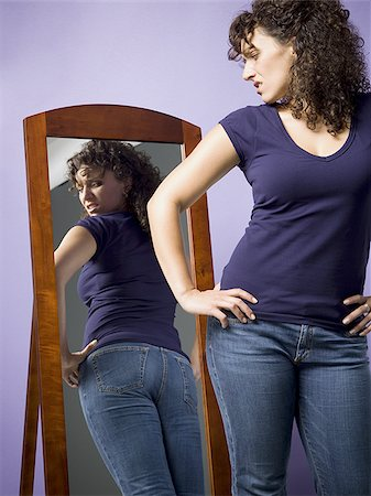 Young woman looking at her buttocks in the mirror Stock Photo - Premium Royalty-Free, Code: 640-02767899