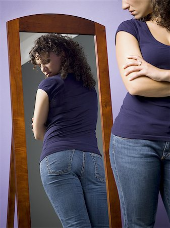 Young woman looking at her buttocks in the mirror Stock Photo - Premium Royalty-Free, Code: 640-02767900