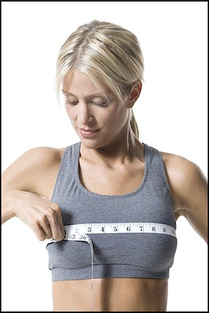 A young woman measuring her chest with a measuring tape Stock Photo - Premium Royalty-Free, Code: 640-02767983
